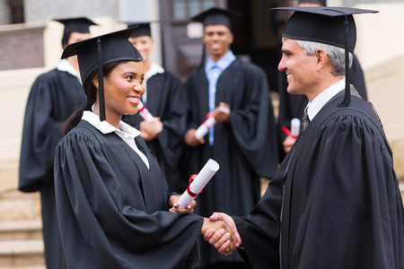 masters degree: smiling afro american female graduate handshaking with dean Stock Photo