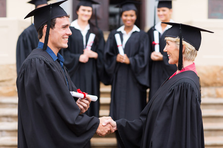 happy young graduate shaking hand with professor photo