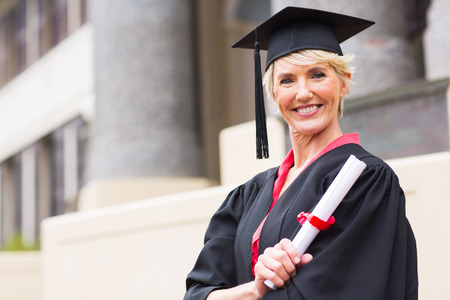 college graduation: happy middle aged woman with graduation cap and gown holding diploma  Stock Photo
