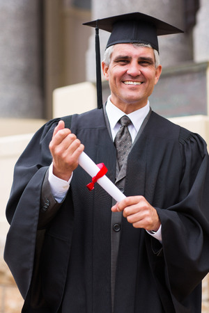 smiling middle aged male graduate in front university building photo