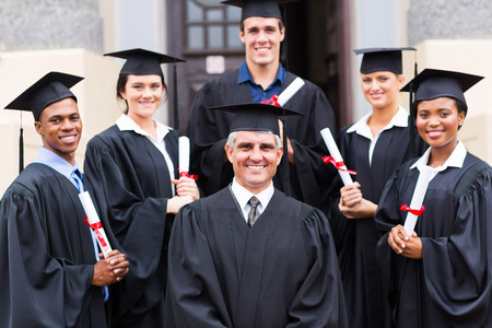 masters degree: dean standing with group of happy graduates outside university