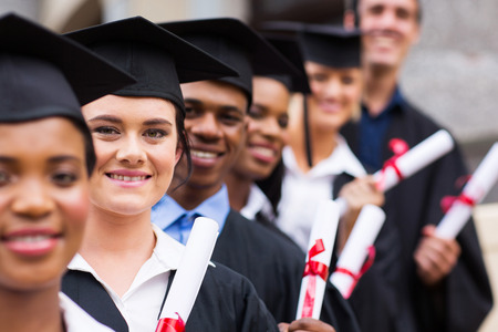 master degree: group of happy college graduates standing in a row Stock Photo