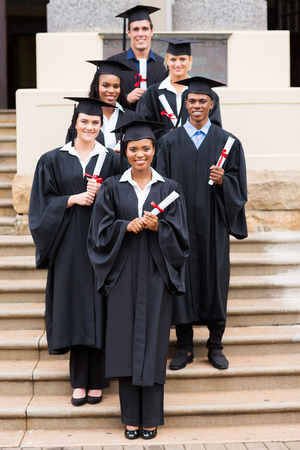 college graduation: group of happy young college graduates in front of school building