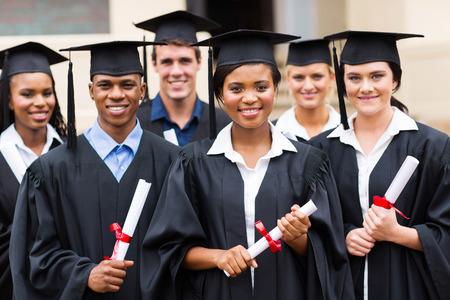 college graduation: portrait of multiracial graduates holding diploma
