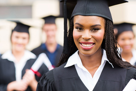 close up portrait of african american female graduate in front of classmates photo