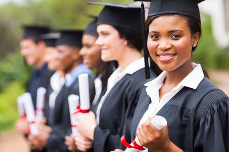 vysoká škola: Pěkně afro žena vysokoškolský absolvent na promoci se spolužáky Reklamní fotografie