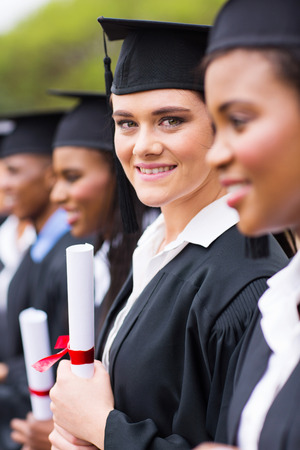 pretty young university graduate standing in a row photo
