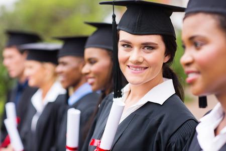 졸업에 친구와 함께 서 웃는 여성 대학 졸업 스톡 콘텐츠