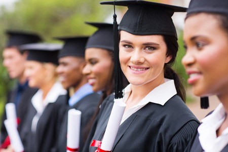 master degree: smiling female college graduate standing with friends at graduation