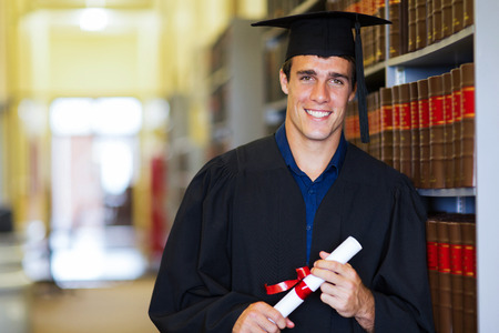 handsome male graduate wearing graduation gown in library photo