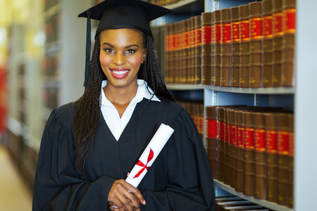pretty african american college student wearing graduation attire in library photo