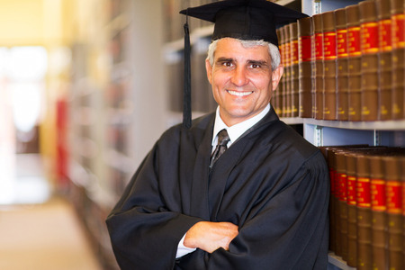 portrait of senior graduate with arms crossed in library photo