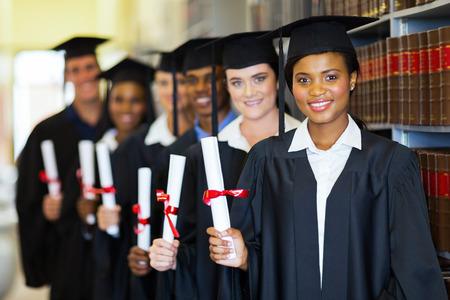 licenciado: feliz grupo de graduados de la celebraci�n diploma en la biblioteca