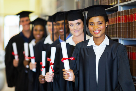 master degree: group of happy graduates holding diploma in library Stock Photo