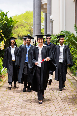 group of happy graduates walking to graduation ceremony photo