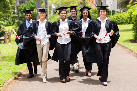 group of cute multiracial graduates walking on college campus Stock Photo