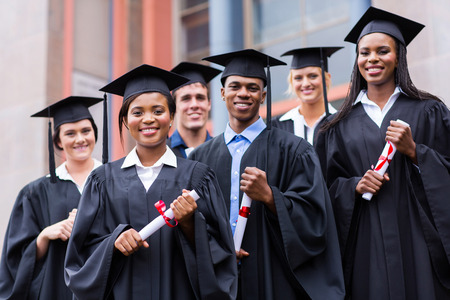 student studying: young graduates standing in front of university building on graduation day