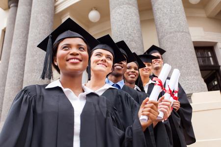 group of happy college graduates on graduation day photo