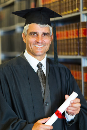 cheerful mid age male law school graduate holding diploma photo
