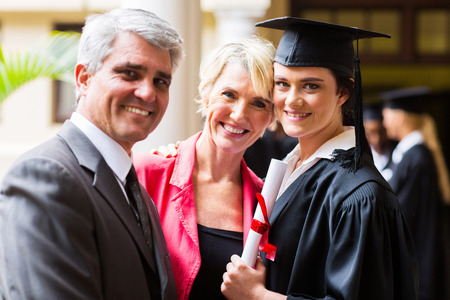 beautiful female college graduate with parents on graduation day Stock Photo