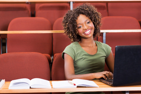 happy african college girl using laptop in class photo