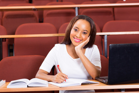 female african university student sitting in classroom looking at the camera photo