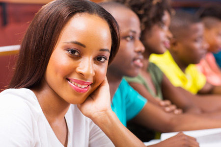 beautiful female african american university student in lecture hall with classmates photo