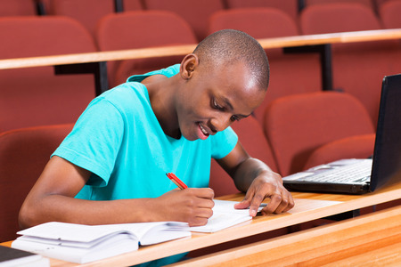 african student: handsome male african college student writing classwork