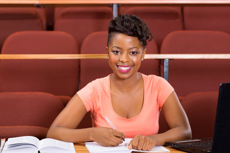 pretty female african american university student sitting in lecture hall photo