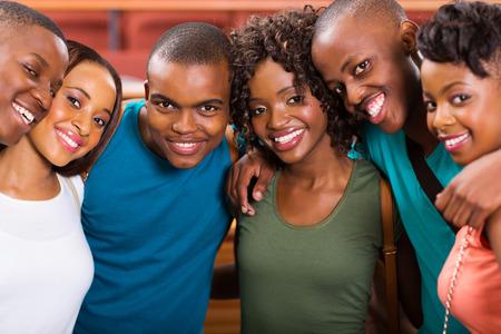 amigos abrazandose: grupo de estudiantes afroamericanos jóvenes felices Foto de archivo
