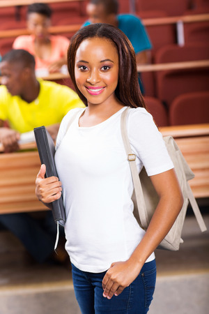 pretty young african american college student standing in classroom photo
