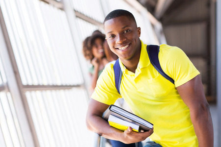 college campus: cheerful male afro american student holding books Stock Photo