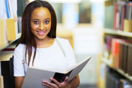 female afro american university student reading book in library photo