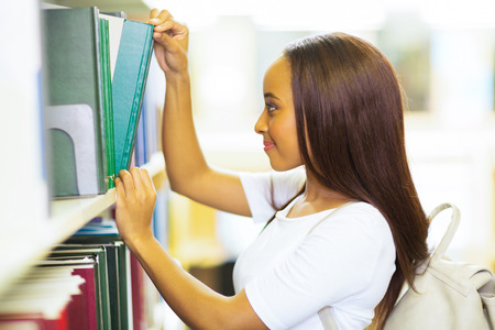 smiling female african college student pulling a library book off shelf photo