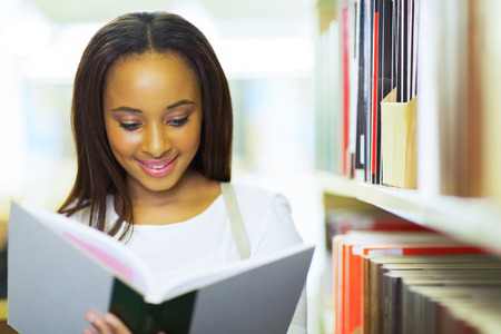 smiling female african american university student reading in library photo