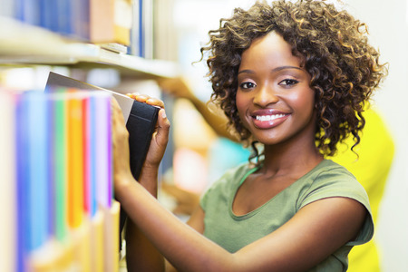 pretty african college girl looking for book in library photo