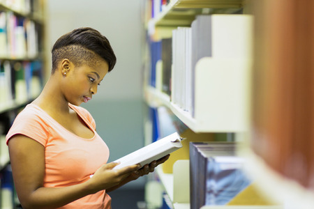 young female african university student reading a book in library photo