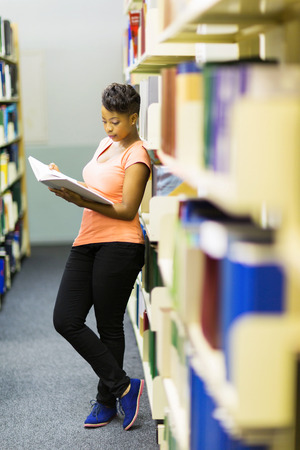 pretty african college girl reading a book in library photo