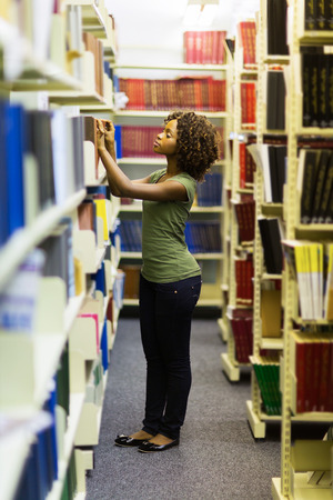 african student: female african college student searching for a book in library
