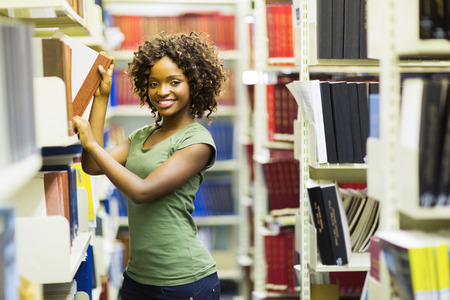 attractive young african american college student searching for books in library photo