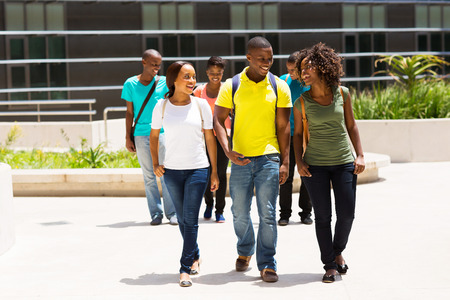 group of happy african american college students walking on modern campus photo