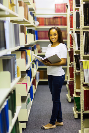 beautiful young african university student reading a book in library photo