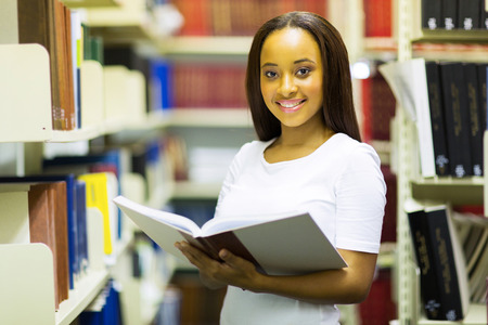 portrait of african american college girl reading in library photo