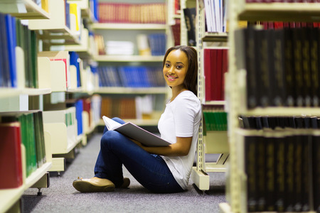 pretty african college girl sitting in library reading