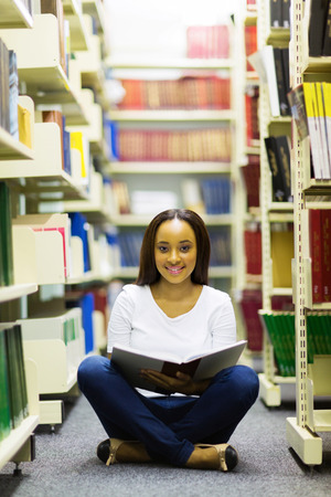 female african student sitting on library floor and reading  photo