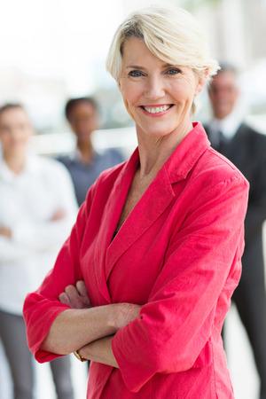confianza: bella mujer de negocios de mediana edad con los brazos cruzados