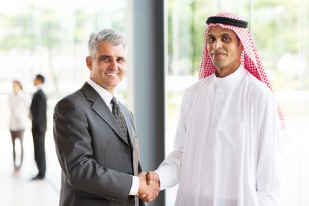 successful senior businessman handshake with Arabian partner photo