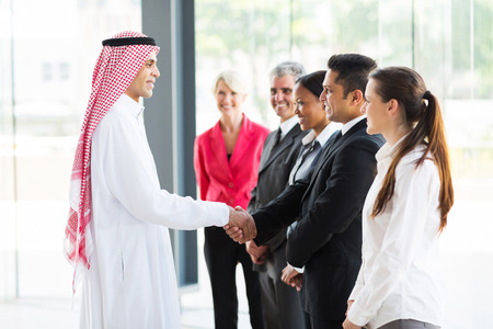 arabian businessman handshaking with group of his employees in office photo