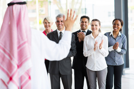 business team applauding to welcome arabian business partner photo