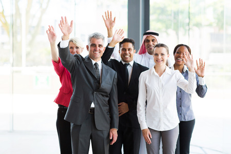 group of happy multicultural businesspeople waving photo